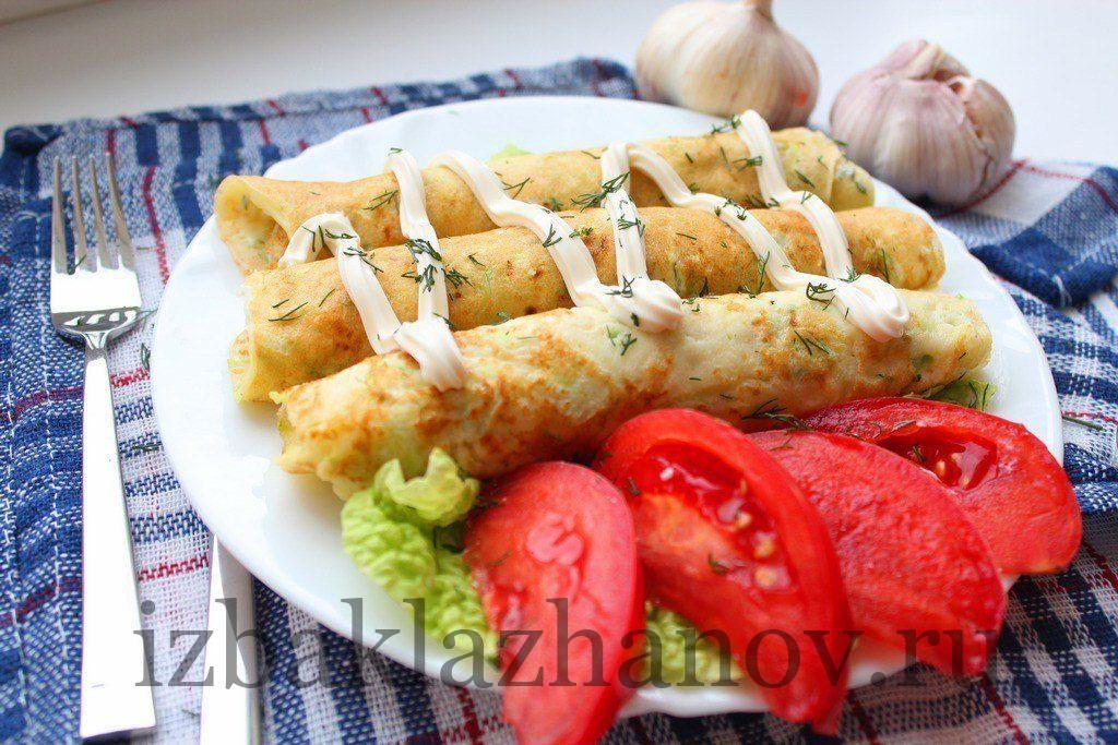 Кабачковые блины на тарелке с помидорами и зеленью